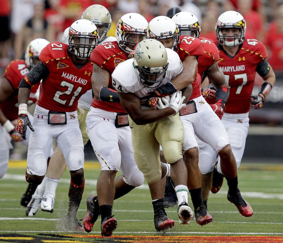 Photo -   William & Mary's Keith McBride (24) runs the ball as Maryland's Dexter McDougle (25) and Alex Twine (35) make the tackle during the second half of an NCAA college football game, Saturday, Sept. 1, 2012, in College Park, Md. Maryland won 7-6. (AP Photo/Luis M. Alvarez)