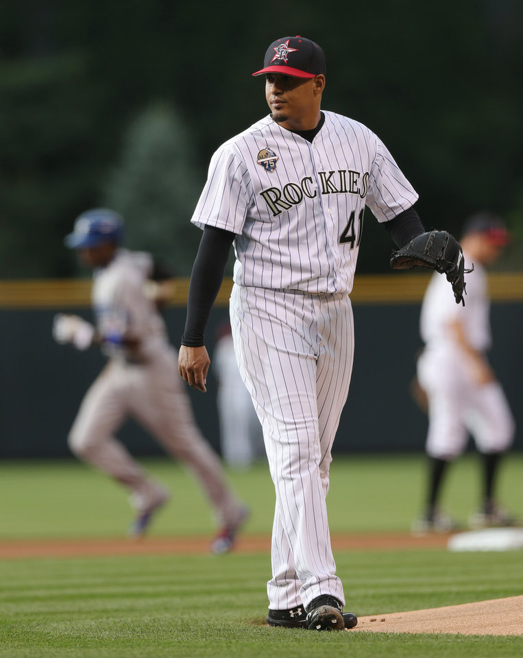 Photo - Colorado Rockies starting pitcher Jair Jurrjens, front, calls for new ball as Los Angeles Dodgers' Yasiel Puig, back left, circles the bases after hitting a two-run home run in the first inning of a baseball game in Denver, Friday, July 4, 2014. (AP Photo/David Zalubowski)