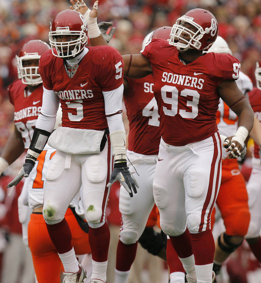 Photo - Oklahoma's Nic Harris (5) and Gerald McCoy (93) react after Harris' sack on Oklahoma State quarterback Zac Robinson during the first half of the college football game between the University of Oklahoma Sooners (OU) and the Oklahoma State University Cowboys (OSU) at the Gaylord Family-Memorial Stadium on Saturday, Nov. 24, 2007, in Norman, Okla. 