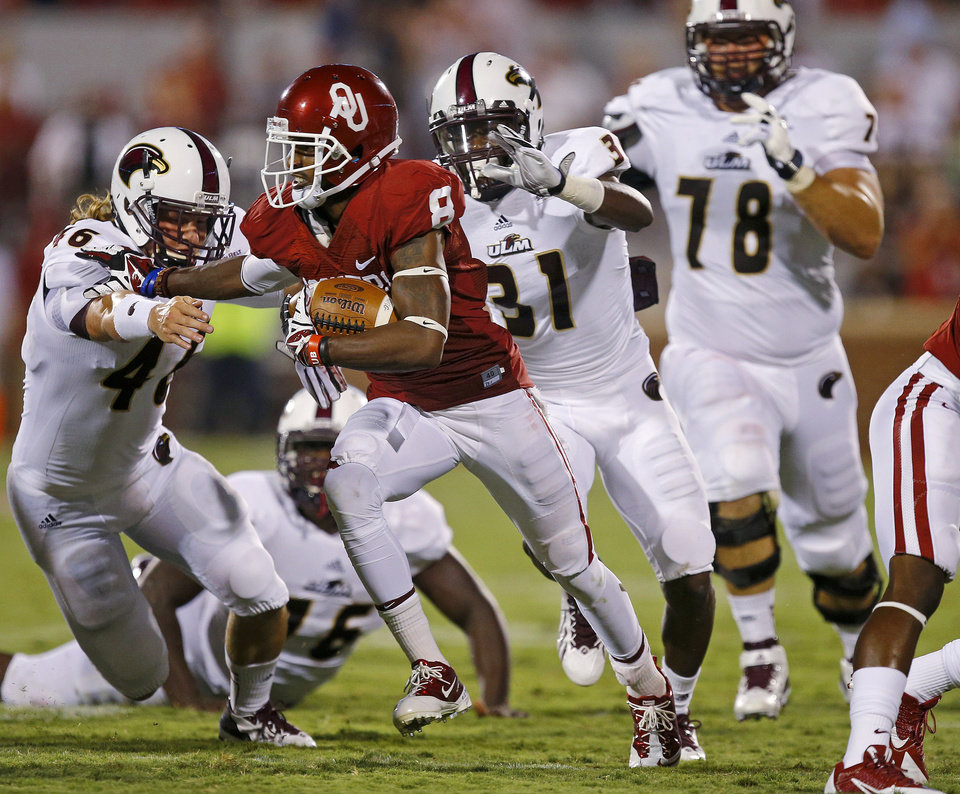 Photo - Oklahoma's Jalen Saunders (8) fights of Louisiana Monroe's Madison Tharp (46) on a long punt return during a college football game between the University of Oklahoma Sooners (OU) and the University of Louisiana Monroe Warhawks at Gaylord Family-Oklahoma Memorial Stadium in Norman, Okla., on Saturday, Aug. 31, 2013. Oklahoma won 34-0. Photo by Bryan Terry The Oklahoman