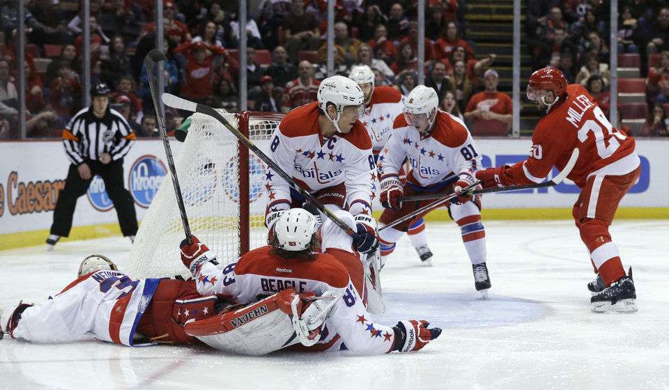 Photo - Detroit Red Wings left wing Drew Miller (20) shoots the puck past the Washington Capitals defense for a goal during the second period of an NHL hockey game in Detroit, Friday, Jan. 31, 2014. (AP Photo/Carlos Osorio)