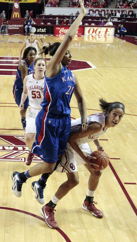 Photo - Kansas Jayhawks' Carolyn Davis (21) is faked on a shot by Oklahoma Sooner's Nicole Griffin (4) as the University of Oklahoma Sooners (OU) play the Kansas Jayhawks in NCAA, women's college basketball at The Lloyd Noble Center on Saturday, March 2, 2013  in Norman, Okla. Photo by Steve Sisney, The Oklahoman