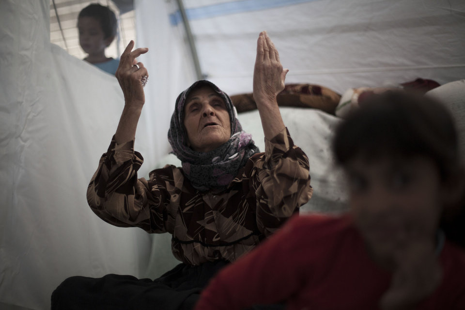 "An elderly Syrian woman, who fled her home with her family due to fighting between government forces and rebels, chants, ""Allah,"" meaning God in Arabic, inside her tent at a refugee camp near the Turkish border, in Azaz, Syria, Sunday, Oct. 7, 2012. (AP Photo/ Manu Brabo)"