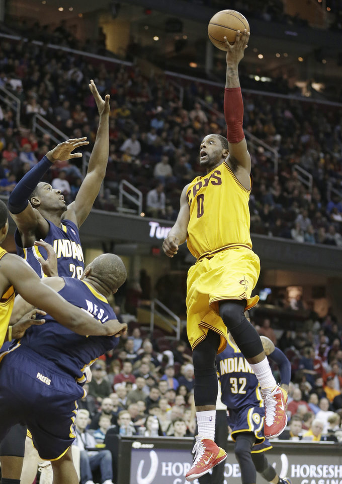 Photo - Cleveland Cavaliers' C.J. Miles (0) jumps to the basket against Indiana Pacers' Ian Mahinmi (28), of France, and David West during the third quarter of an NBA basketball game Sunday, Jan. 5, 2014, in Cleveland. The Pacers won 82-78. (AP Photo/Tony Dejak)