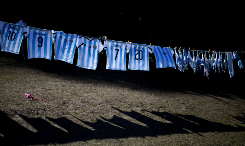 Photo - Argentina's national soccer team T-shirts hang for sale outside the Argentine Soccer Association before the team heads the airport in Buenos Aires, Argentina, Monday, June 9, 2014. Argentina's team is leaving Monday to compete in the Brazil's 2014 soccer Word Cup. (AP Photo/Natacha Pisarenko)