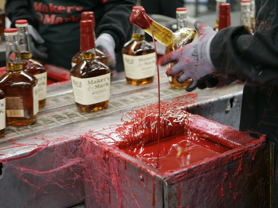 Photo - FILE - In this Wednesday, April 8, 2009, file photo, a bottle of Maker's Mark bourbon is dipped in red wax during a tour of the distillery in Loretto, Ky. Kentucky bourbon makers have stashed away their largest stockpiles in more than a generation due to resurgent demand for the venerable brown spirit. (AP Photo/Ed Reinke, File)