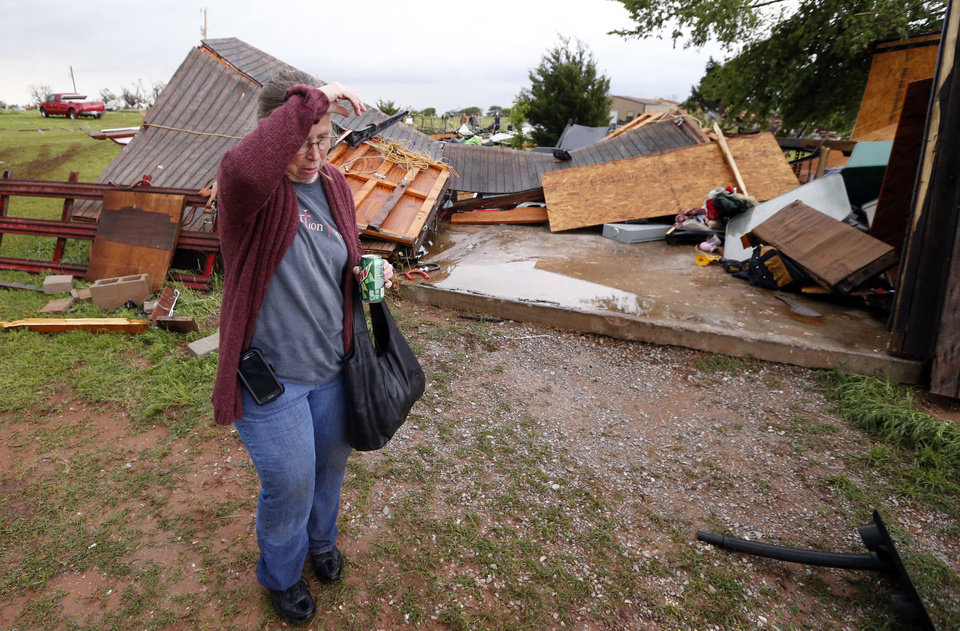 Photo - Denise Stark walks worries about a second storm as she walks past demolished buildings at her home after a tornado ripped through Bridge Creek, Okla. on Wednesday, May 6, 2015.  Photo by Steve Sisney, The Oklahoman
