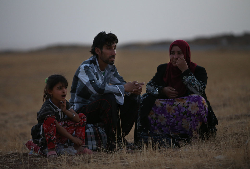 Photo - A fleeing Iraqi family, who fled from Mosul, settle in a field near a Kurdish security forces checkpoint, in the Khazer area between the Iraqi city of Mosul and the Kurdish city of Irbil, northern Iraq, Wednesday June 25, 2014. Sunni insurgents who seized Iraq's second largest city attacked a nearby Christian village on Wednesday, bringing their fight closer to the largely Kurdish regions of northern Iraq which had remained so far largely untouched from the chaos sweeping the country. (AP Photo/Hussein Malla)
