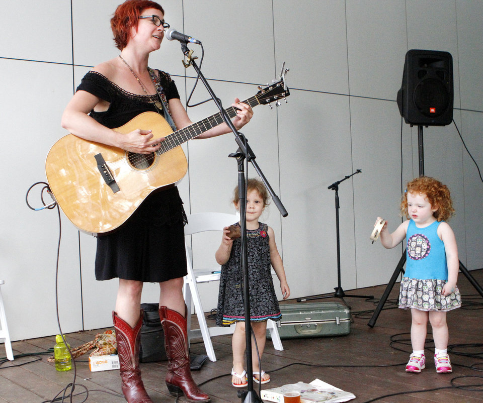 Photo - Carter Sampson plays her guitar and stomps her feet along with two-year-olds Hadley Mae Zahl (middle) and Charlotte Greenhaw (right) at the OK Chefs Relief in the Myriad Gardens of Oklahoma City on May 27, 2013. Photo by KT King, The Oklahoman