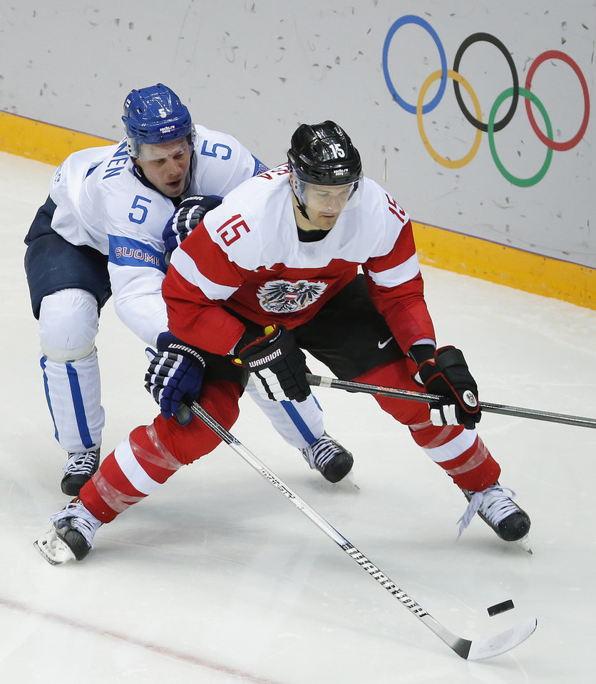 Photo - Finland defenseman Lasse Kukkonen reaches for he puck against Austria forward Manuel Latusa in the second period of a men's ice hockey game at the 2014 Winter Olympics, Thursday, Feb. 13, 2014, in Sochi, Russia. (AP Photo/Mark Humphrey)
