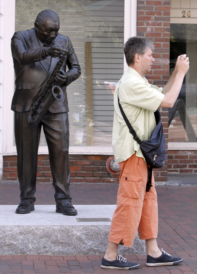 Photo -   FILE-In this July 27, 2010, file photo, a visitor takes pictures in front of the statue of Big Joe Burrell on Church St. in Burlington, Vt.Mountain and lake views along with fall foliage can be had for free in Vermont's largest city of Burlington, which feels more like a big town than a city. (AP Photo/Toby Talbot)
