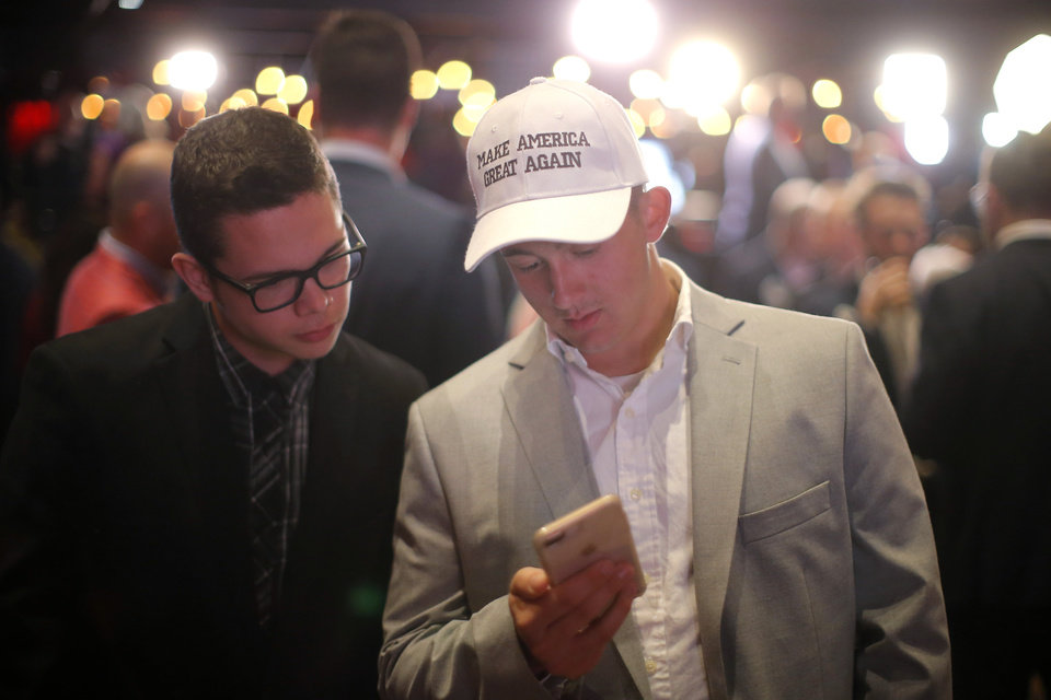 Photo - Preston Parks, left a University of Oklahoma student from Stratford, Okla., and Justin Vakulick an OU student from Blanchard, Okla., check election results during the Republican election night watch party for the 2018 elections at the Bricktown Events Center in Oklahoma City, Nov. 6, 2018. Photo by Bryan Terry, The Oklahoman