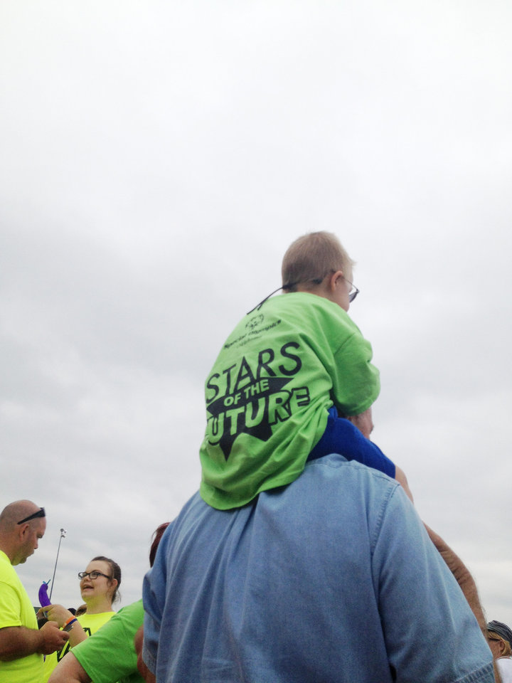 Photo - Looking up. A child sits atop shoulders wearing an event T-shirt from the Summer Games in Stillwater May 9, 2013. Photo by Cade Godfrey, Special Correspondent