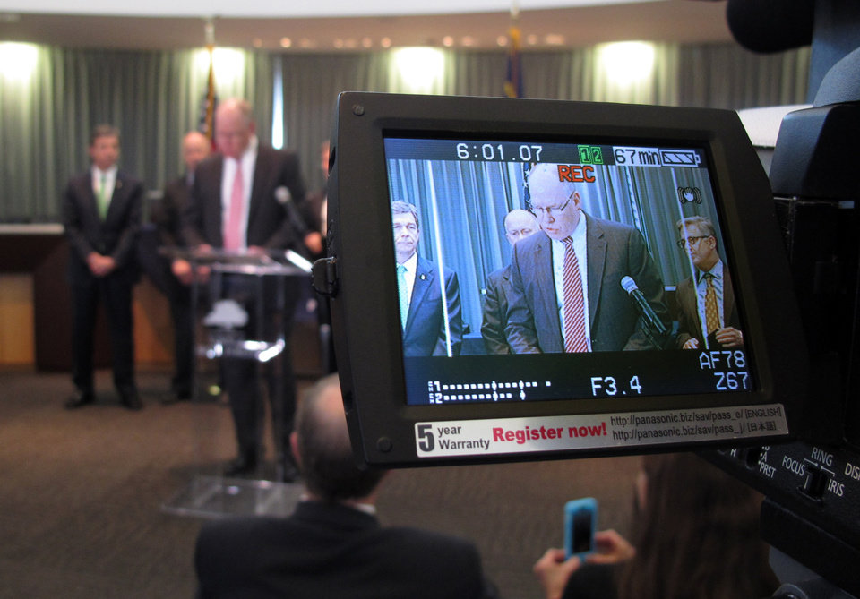 Photo - John Strong, FBI special agent in charge of North Carolina, is displayed on a camera monitor as he addresses the media during a news conference at the Wake Forest Town Hall on Thursday, April 10, 2014, in Wake Forest, N.C. Strong said the kidnapping of Frank Arthur Janssen was related to his daughter's prosecution of North Carolina prisoner Kelvin Melton, who is serving a life sentence for his 2012 conviction for being a habitual felon. Melton, 49, was also convicted of assault with a deadly weapon with intent to kill.  (AP Photo/Allen G. Breed)