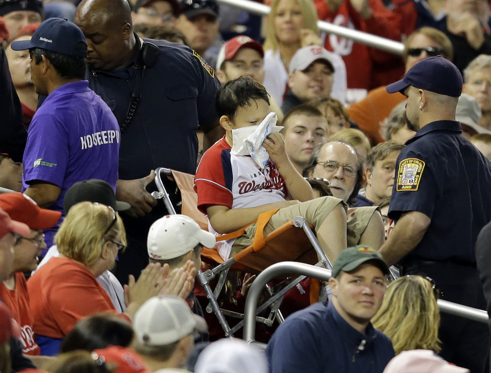 Photo - A fan, center, is taken out of the stands after being hit by a foul ball off the bat of Washington Nationals' Bryce Harper during the third inning of a baseball game against the Philadelphia Phillies at Nationals Park, Saturday, May 25, 2013, in Washington. (AP Photo/Alex Brandon)