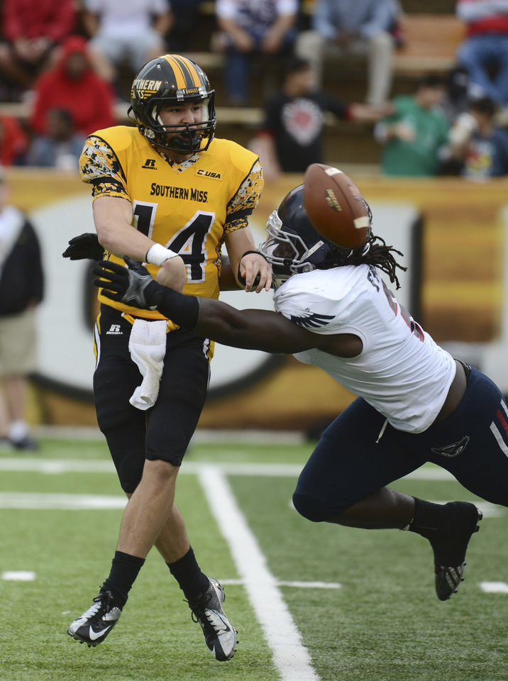 Photo - FILE -  In this Nov. 16, 2013, file photo, Southern Mississippi quarterback Nick Mullens (14) throws the ball away before Florida Atlantic defensive lineman Brandin Bryant (2) tackles him in the fourth quarter of an NCAA college football game in Hattiesburg, Miss Bryant grew up hearing about the football exploits of his grandfather Charles Bryant at Nebraska, and he dreamed of the day he, too, would play at Lincoln's Memorial Stadium. (AP Photo/Steve Coleman, File)