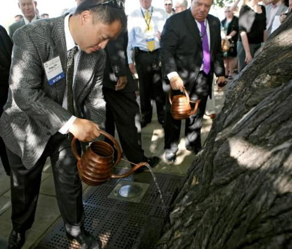 Mike Gin, mayor of Redondo Beach, California, waters the Survivor  Tree  during a service at the Oklahoma City National Memorial and Museum in Oklahoma City on Sunday, June 13, 2010. The ceremony was one of the events attended by mayors from around the country during the U.S. Conference of Mayors. Photo by John Clanton