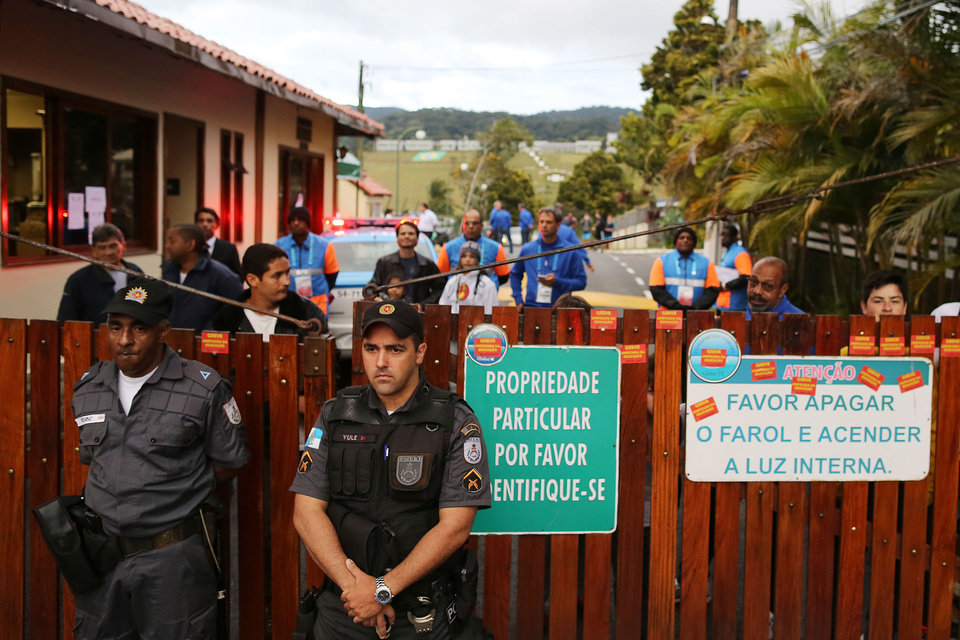 Photo - Police officers stand guard at the entrance of the Granja Comary training center, during a teachers's protest in front of  where the Brazilian national soccer team will train and reside during the World Cup, in Rio de Janeiro, Brazil, Monday, May 26, 2014. Demonstrators are protesting against the money being spent by the government on the World Cup. (AP Photo/Leo Correa)