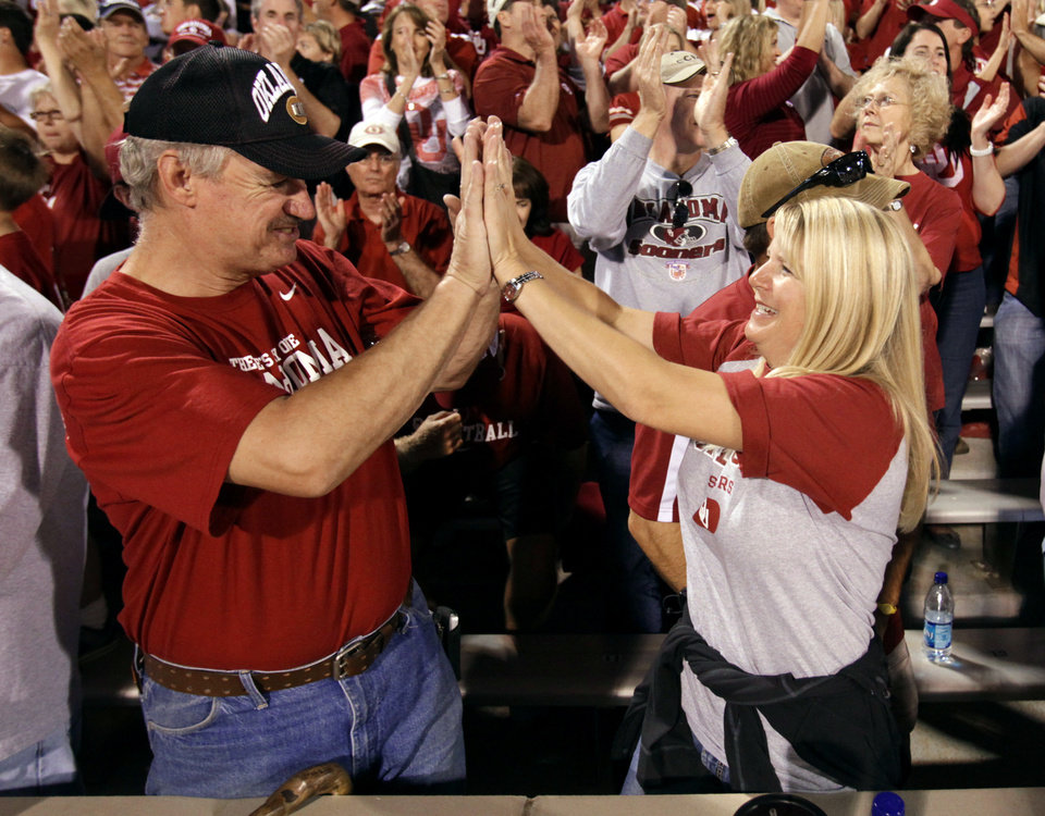 Photo - Friends through seating, Rod Gross, Moore, and Stefanie Edney, Oklahoma City, celetrate a touchdown during the first half of the college football game between the University of Oklahoma Sooners (OU) and the Iowa State Cyclones (ISU) at the Glaylord Family-Oklahoma Memorial Stadium on Saturday, Oct. 16, 2010, in Norman, Okla.  Photo by Steve Sisney, The Oklahoman