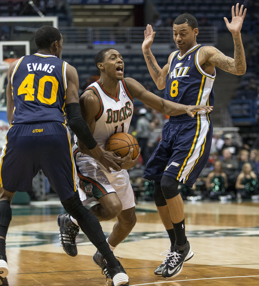 Photo - Milwaukee Bucks' Brandon Knight, center, is fouled by Utah Jazz Diante Garrett, right, with teammate Jeremy Evans, left, during the first half of an NBA basketball game Monday, March 3, 2014, in Milwaukee. (AP Photo/Tom Lynn)