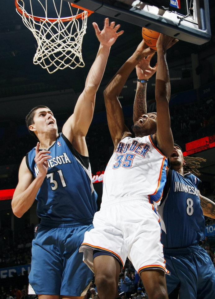 Photo - Oklahoma City's Kevin Durant (35) makes a shot next to Minnesota's Darko Milicic (31) as Michael Beasley (8) fouls Durant during the NBA basketball game between the Minnesota Timberwolves and the Oklahoma City Thunder at the Oklahoma City Arena, Monday, November 22, 2010, in Oklahoma City. The Thunder won, 117-107. Photo by Nate Billings, The Oklahoman