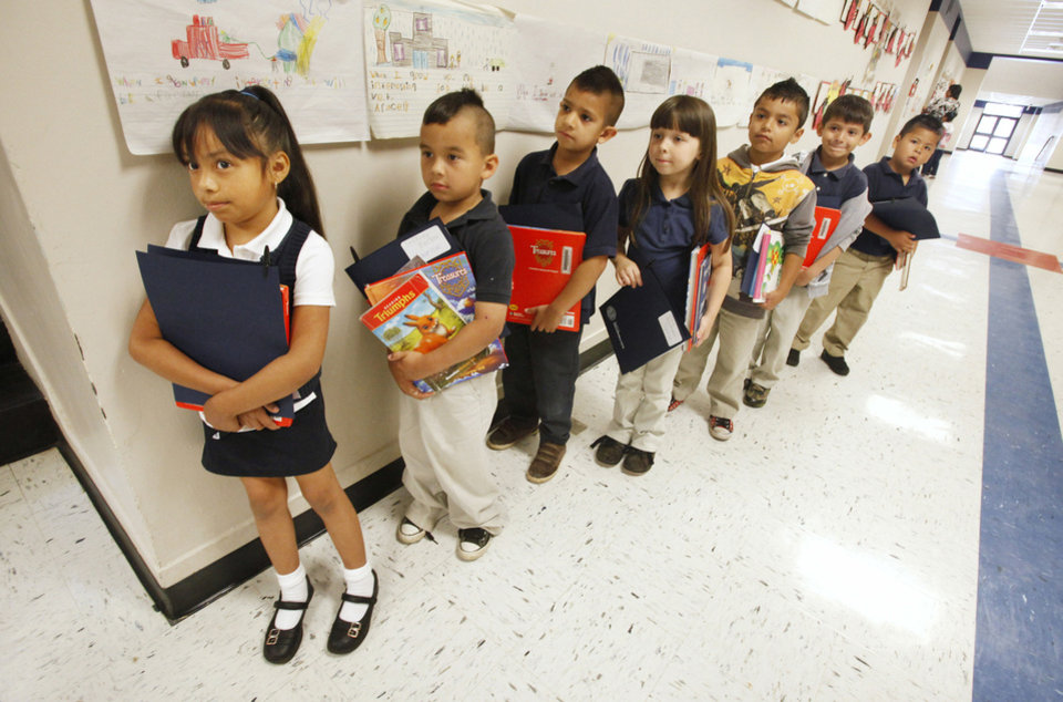 Photo - First grader Arline Mena, 6, far left, lines up with classmates Thursday at Heronville Elementary School in Oklahoma City. A reading buddies program with students and city employees is one of the programs with roots in a task force of city council members and school officials.  PAUL B. SOUTHERLAND - The Oklahoman