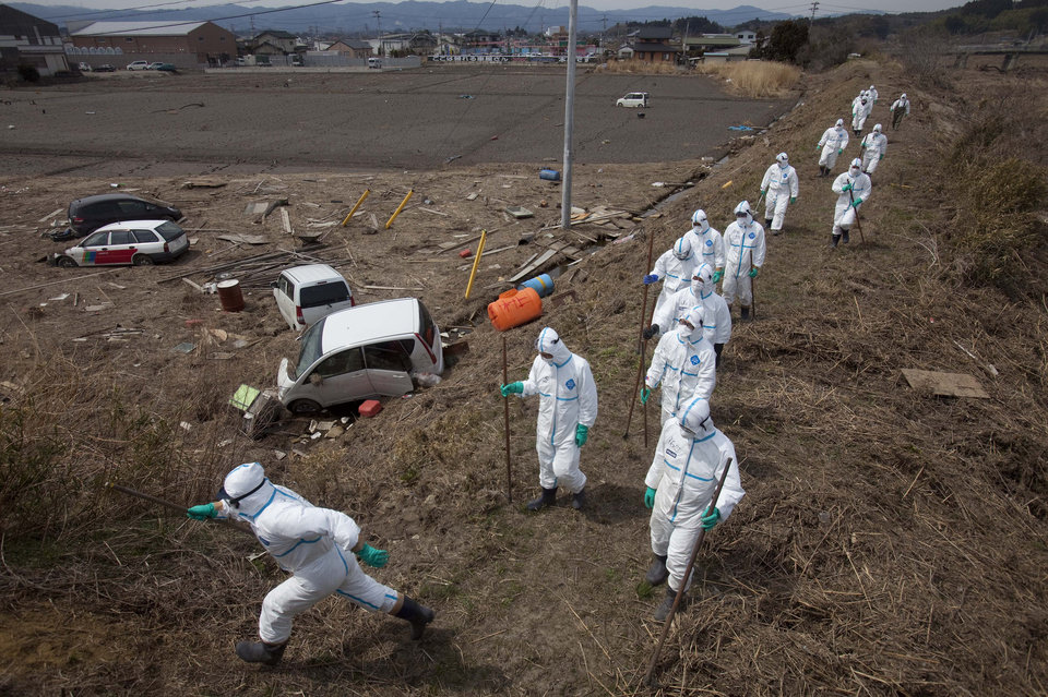 FILE - In this April 7, 2011 file photo, Japanese police, wearing suits to protect them from radiation, search for victims inside the deserted evacuation zone, established for the 20 kilometer radius around the Fukushima Dai-ichi nuclear reactors, in Minamisoma, Fukushima prefecture, Japan. People exposed to the highest doses of radiation during the Fukushima nuclear plant disaster in 2011 may have a slightly higher risk of cancer that is so small it probably won�t even be detectable, according to a new report from the World Health Organization released on Thursday Feb. 28, 2013. (AP Photo/David Guttenfelder, File)