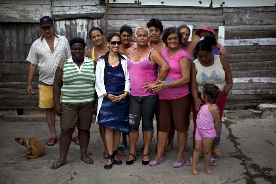 "Adela Hernandez, 48, center, poses for a photo neighbors in the village of Caibarien, Cuba, Friday, Nov. 16, 2012. Hernandez, a biologically male Cuban who has lived as a female since childhood, served two years in prison in the 1980s for ""dangerousness"" after her own family denounced her sexuality. This month she made history by becoming the first known transgender person to hold public office in Cuba, winning election as a delegate to the municipal government of Caibarien in the central province of Villa Clara. (AP Photo/Ramon Espinosa)"