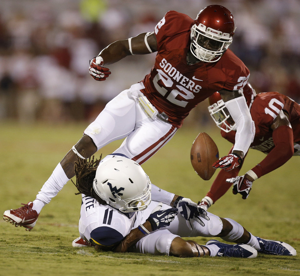 Photo - West Virginia's Kevin White (11) loses the ball by Oklahoma's Cortez Johnson (22) and Quentin Hayes (10) during a college football game between the University of Oklahoma Sooners (OU) and the West Virginia University Mountaineers at Gaylord Family-Oklahoma Memorial Stadium in Norman, Okla., on Saturday, Sept. 7, 2013. Oklahoma won 16-7. Photo by Bryan Terry, The Oklahoman