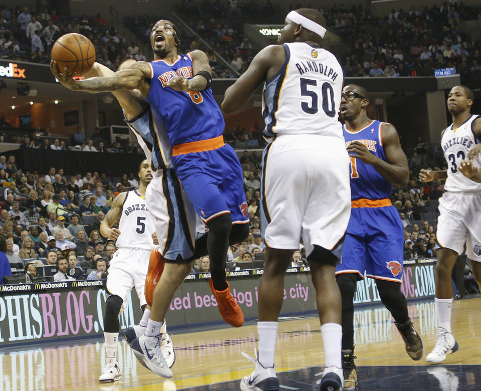 Photo - New York Knicks guard J.R. Smith (8) drives to the basket against Memphis Grizzlies forward Zach Randolph (50) and Nick Calathes, back, in the first half of an NBA basketball game, Tuesday, Feb. 18, 2014, in Memphis, Tenn. (AP Photo/Lance Murphey)