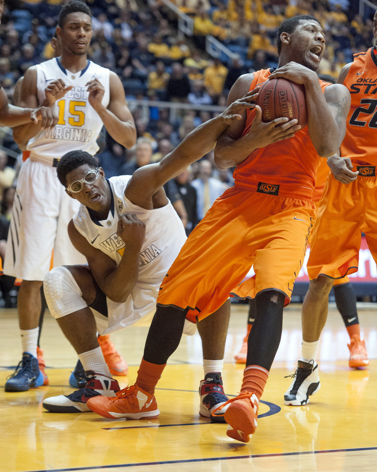 Photo - Oklahoma State's Marcus Smart, right, battles West Virginia's Devin Williams for the ball during the second half of an NCAA college basketball game Saturday, Jan. 11, 2014, in Morgantown, W.Va. Oklahoma State won 73-72. (AP Photo/Andrew Ferguson)