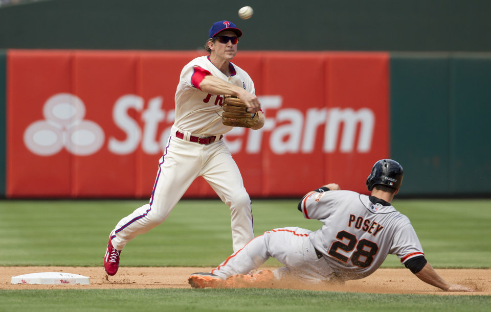 Photo - Philadelphia Phillies second baseman Chase Utley, left, throws the ball to first base as San Francisco Giants' Buster Posey, right, slide towards him, during the fourth inning of a baseball game, Thursday, July 24, 2014, in Philadelphia. Utley did not complete the double play. (AP Photo/Chris Szagola)