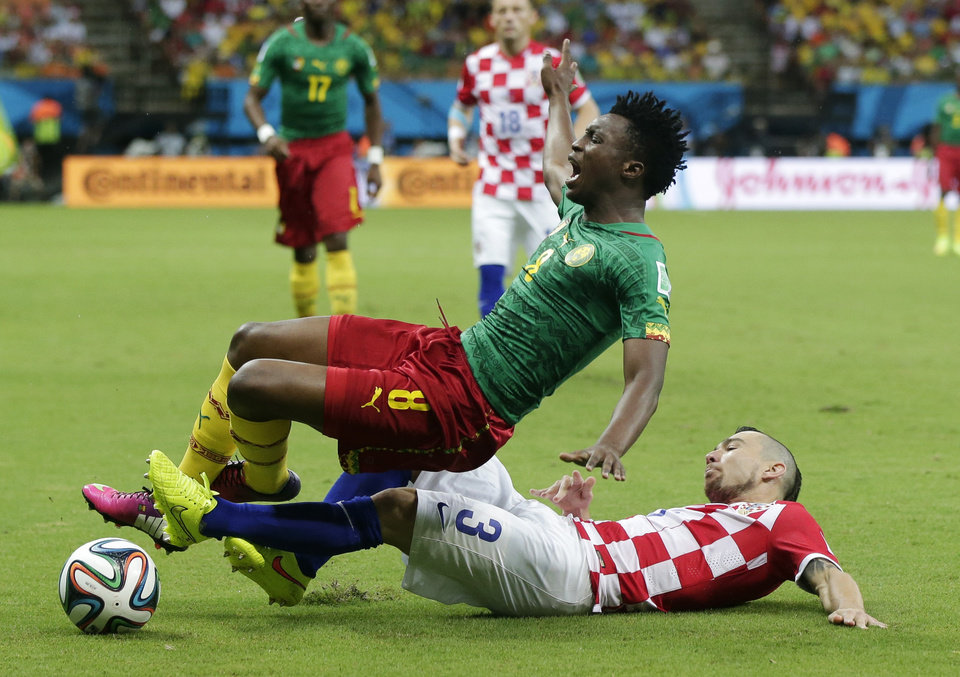 Photo - Croatia's Danijel Pranjic, right, slides underneath Cameroon's Benjamin Moukandjo during the group A World Cup soccer match between Cameroon and Croatia at the Arena da Amazonia in Manaus, Brazil, Wednesday, June 18, 2014.  (AP Photo/Marcio Jose Sanchez)