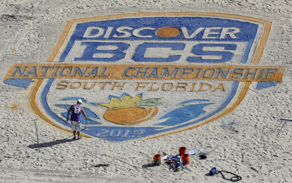 Photo - An artist puts the finishing touches on the BCS National Championship logo on the beach Sunday, Jan. 6, 2013, in Fort Lauderdale, Fla. Notre Dame takes on Alabama for the National Championship in an NCAA college football game on Monday night. (AP Photo/Chris O'Meara)