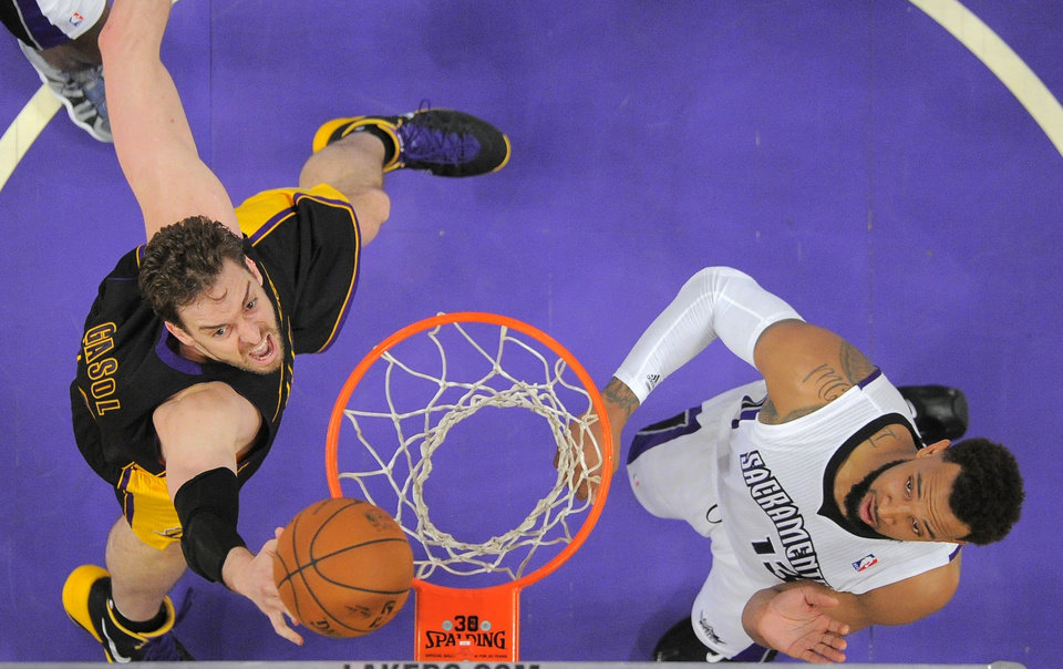 Photo - Los Angeles Lakers center Pau Gasol, left, of Spain, puts up a shot as Sacramento Kings forward Derrick Williams defends during the first half of an NBA basketball game, Friday, Feb. 28, 2014, in Los Angeles. (AP Photo/Mark J. Terrill)