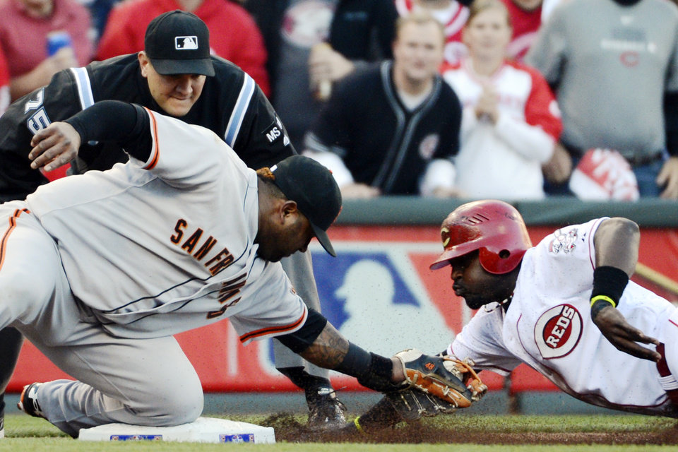 Photo -   San Francisco Giants third baseman Pablo Sandoval tags out Cincinnati Reds' Brandon Phillips at third base in the first inning during Game 3 of the National League division baseball series, Tuesday, Oct. 9, 2012, in Cincinnati. (AP Photo/Michael Keating)