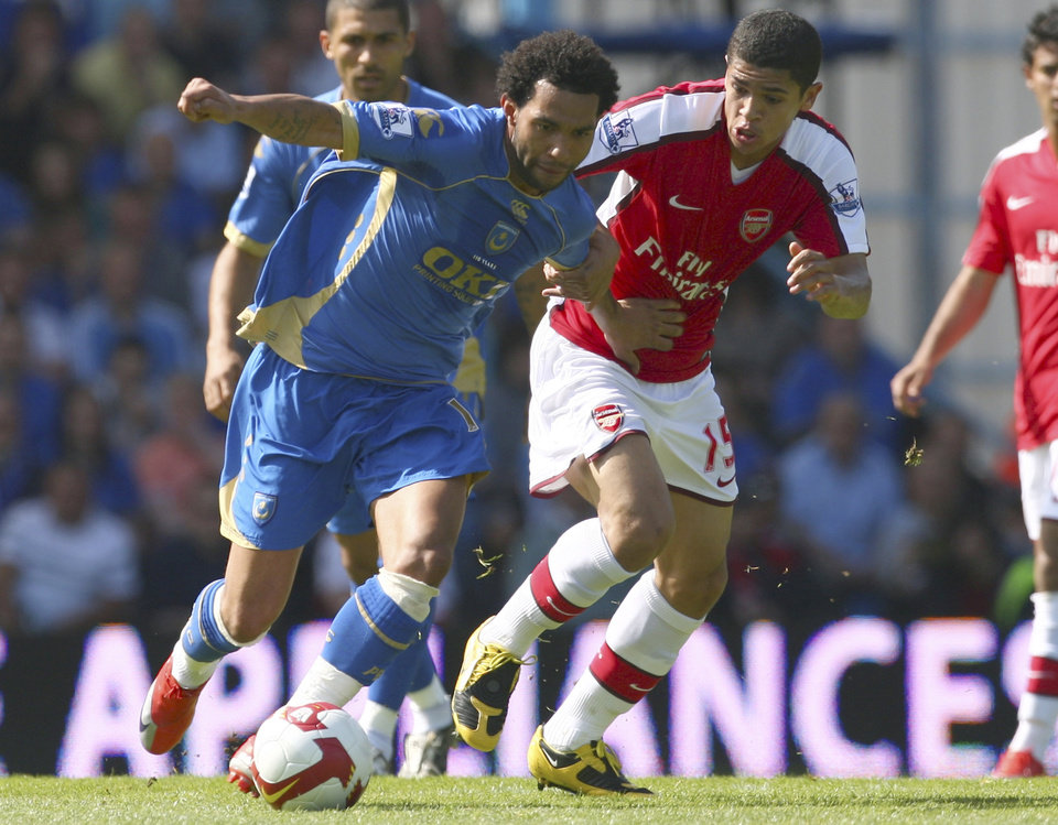 FILE - This is a Saturday May 2, 2009. file photo of the then Portsmouth player Jermaine Pennant, left, as he grapples with Arsenal's Denilson during their English Premier League soccer match at the Fratton Park Stadium, Portsmouth, England. Police in Manchester said Wednesday May 2, 2012 that Jermaine Pennant now playing for Stoke City has been charged on suspicion of assaulting a woman in a Manchester nightclub on Sunday. (AP Photo/Tom Hevezi, File)