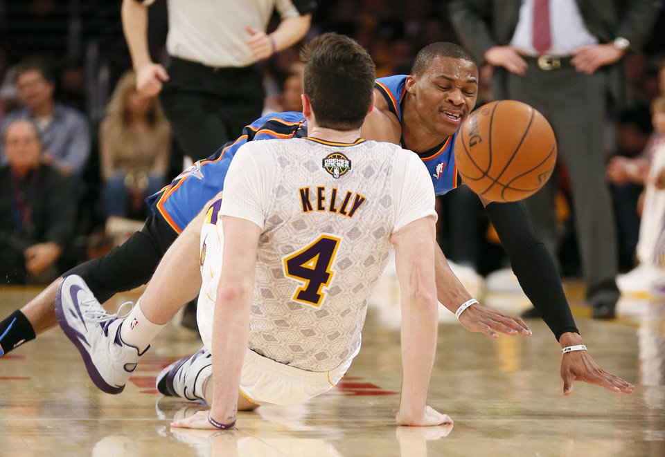 Photo - Oklahoma City Thunder point guard Russell Westbrook is called for an offensive foul and then a technical foul after colliding with Los Angeles Lakers power forward Ryan Kelly (4) during the first half of an NBA basketball game in Los Angeles, Sunday, March 9, 2014. (AP Photo/Danny Moloshok)