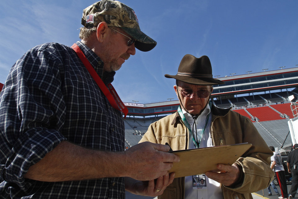 Photo - Car owner Jack Roush, right, signs an autograph before practice for the NASCAR Sprint Cup series auto race at Bristol Motor Speedway on Friday, March 14, 2014, in Bristol, Tenn. (AP Photo/Wade Payne)
