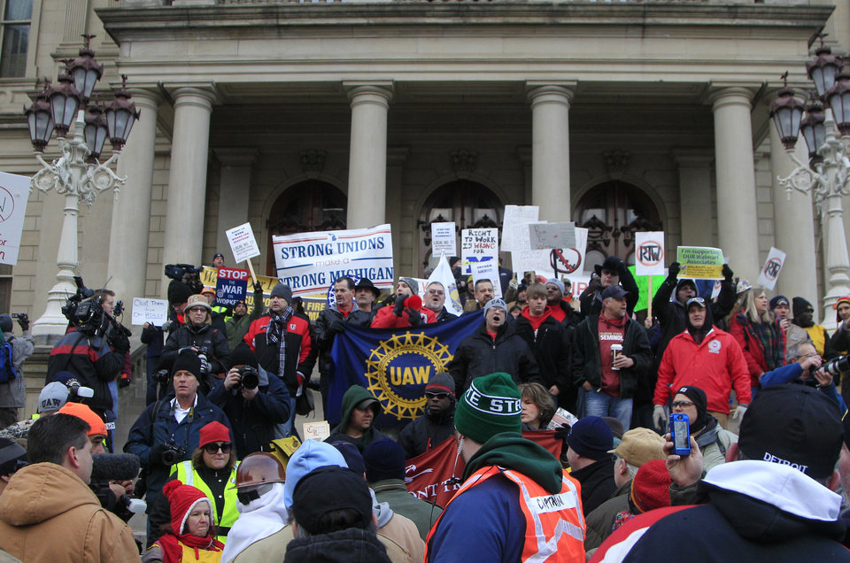 Photo - Thousands of protesters gather for a rally on the State Capitol grounds in Lansing, Mich., Tuesday, Dec. 11, 2012. The crowd is protesting right-to-work legislation that was passed by the state legislature last week.  Michigan will become the 24th right-to-work state, banning requirements that nonunion employees pay unions for negotiating contracts and other services. (AP Photo/Carlos Osorio)