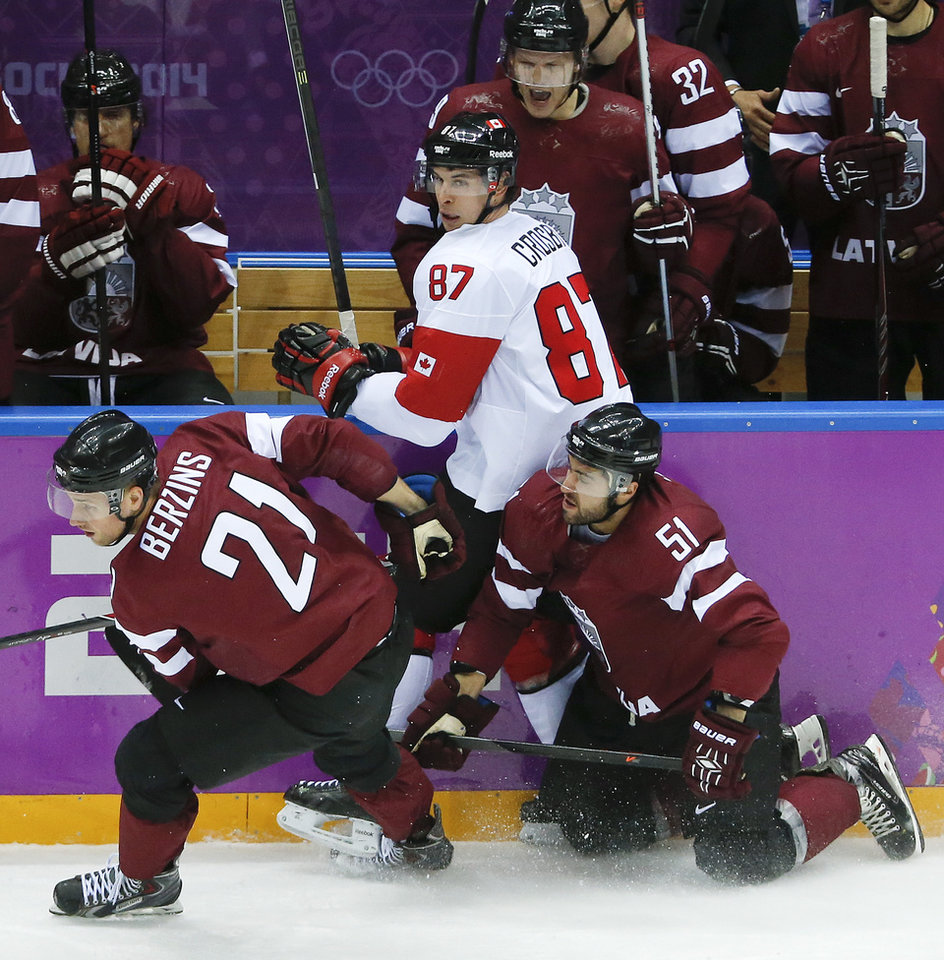 Photo - Latvia forward Armands Berzins and forward Koba Jass collide with Canada forward Sidney Crosby during the second period of a men's quarterfinal ice hockey game at the 2014 Winter Olympics, Wednesday, Feb. 19, 2014, in Sochi, Russia. (AP Photo/Mark Humphrey)