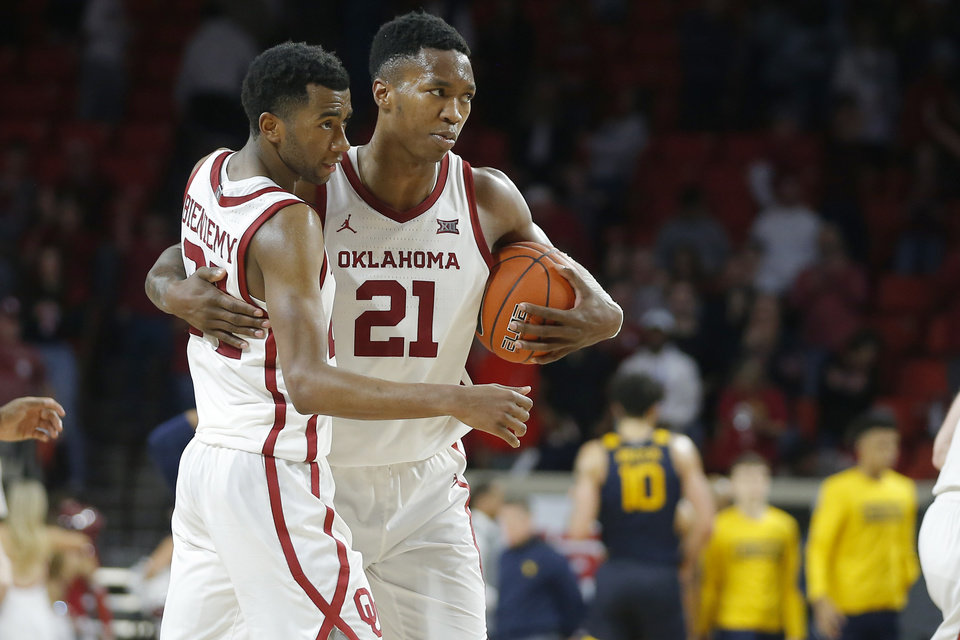 Photo - Oklahoma's Kristian Doolittle (21) and Jamal Bieniemy (24) hug after an NCAA mens college basketball game between the University of Oklahoma Sooners (OU) and the West Virginia Mountaineers at the Lloyd Noble Center in Norman, Okla.,Saturday, Feb. 8, 2020. Oklahoma won 69-59. [Bryan Terry/The Oklahoman]