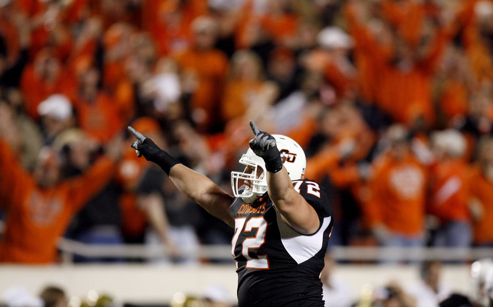 Photo - OSU's Andrew Mitchell (72) celebrates a touchdown during the college football game between Oklahoma State University (OSU) and the University of Colorado (CU) at Boone Pickens Stadium in Stillwater, Okla., Thursday, Nov. 19, 2009. Photo by Sarah Phipps, The Oklahoman