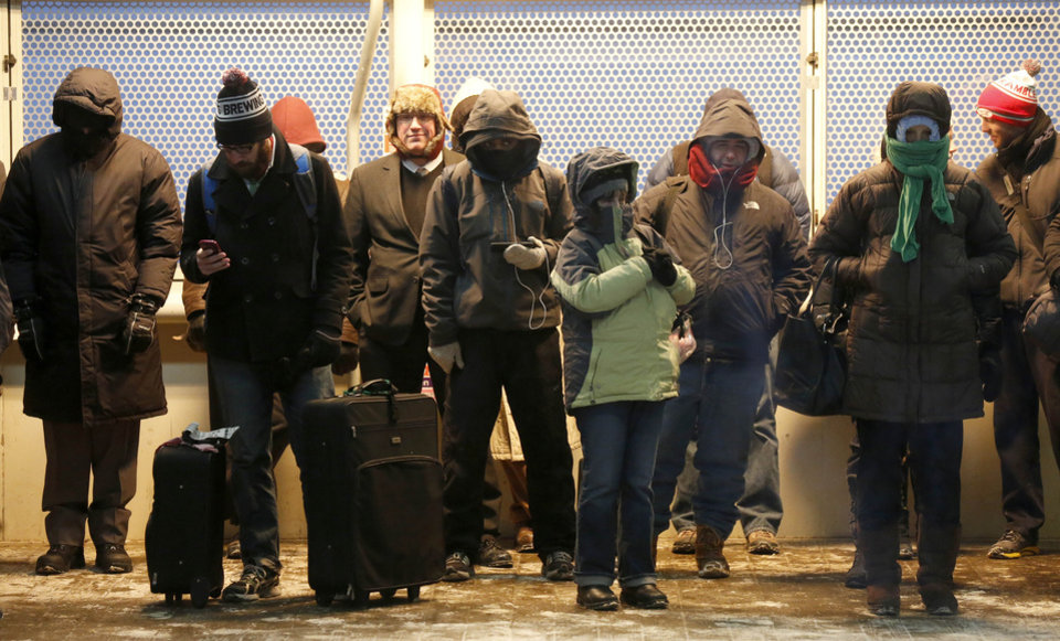 Photo - Commuters gather under warming lamps on one of  Chicago's famous