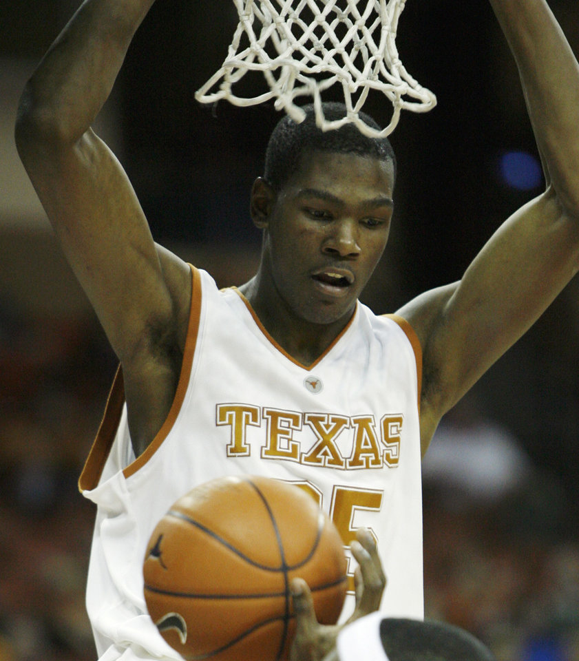 Photo - Texas forward Kevin Durant looks down on a defender after jamming in two points during second half action in their men's college basketball game Tuesday, Jan. 2, 2007, in Austin, Texas. The coaches in the Big 12 will have to forgive the freshman for turning the league into his personal playground. He just wants to have some fun in the conference while he can. (AP Photo/Harry Cabluck) ORG XMIT: AT106