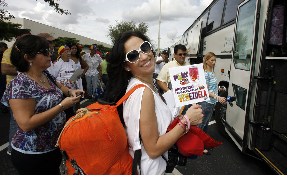 Photo -   Adrea Leon holds a sign saying she supports the elections in Venezuela as she boards one of fifty buses traveling to New Orleans from Miami to vote in the Venezuelan election Saturday Oct. 6th, 2012. The Venezuelan government closed the down its consulate in Miami where the largest population of Venezuelans reside in the United States.(AP Photo/Jeffrey M. Boan)
