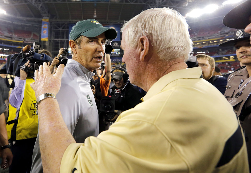 Photo - Central Florida head coach George O'Leary, right, greets Baylor head coach Art Briles at mid-field after the Fiesta Bowl NCAA college football game against Baylor, Wednesday, Jan. 1, 2014, in Glendale, Ariz. Central Florida won 52-42.  (AP Photo/Matt York)