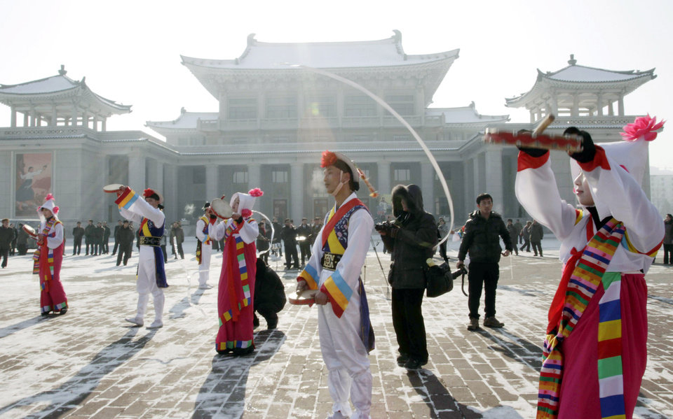 Photo - North Korean youths in traditional Korean outfit play instruments in front of the Pyongyang Grand Theatre in Pyongyang, North Korea, to celebrate a rocket launch on Wednesday, Dec. 12, 2012. North Korea appeared to successfully fire a long-range rocket Wednesday, defying international warnings as the regime of Kim Jong Un pushes forward with its quest to develop the technology needed to deliver a nuclear warhead. (AP Photo/Jon Chol Jin) ORG XMIT: PYO106