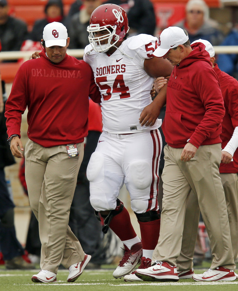 Oklahoma's Nila Kasitati (54) is helped off the field after being hurt on a play during a college football game between the University of Oklahoma (OU) and Texas Tech University at Jones AT&T Stadium in Lubbock, Texas, Saturday, Oct. 6, 2012. OU won, 41-20. Photo by Nate Billings, The Oklahoman