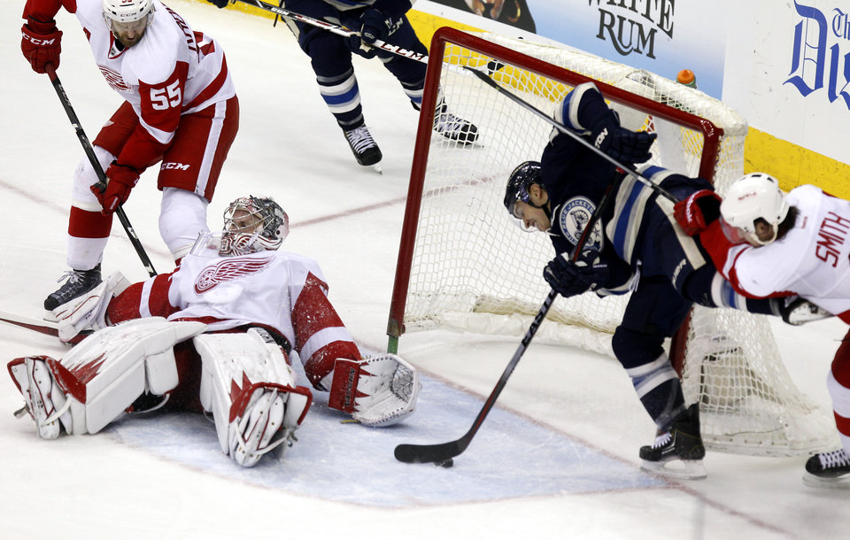 Photo - Columbus Blue Jackets' Cam Atkinson (13) scores a goal against Detroit Red Wings goalie Jimmy Howard (35), Niklas Kronwall (55), of Sweden, and Brendan Smith (2) in the third period of an NHL hockey game in Columbus, Ohio, Tuesday, March 25, 2014. Columbus won 4-2. (AP Photo/Paul Vernon)